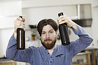 Man in kitchen holding two bottles of beer - FMKF001010