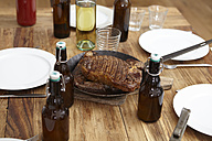 Steak in frying pan and beer bottles on wooden table - FMKF001012