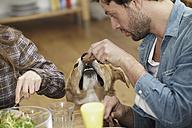 Man eating at table feeding dog - FMKF001101