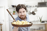 Man in kitchen holding pan with potatoes - FMKF001043