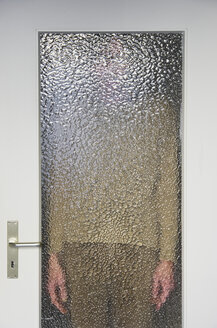 Man standing behind closed door with ribbed glass pane - MUF001453