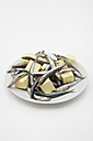Plate of anchovies (Engraulidae) and pieces of butter on white ground - MUF001452