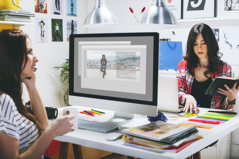 Two female fashion bloggers sitting at desk in the office - EBSF000038