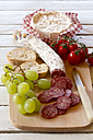 Chopped salami, green grapes, camembert, tomatoes and baguette on chopping board - SARF000294