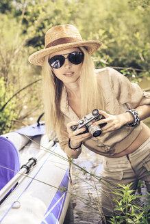 Blond woman with camera at a boat - VTF000128