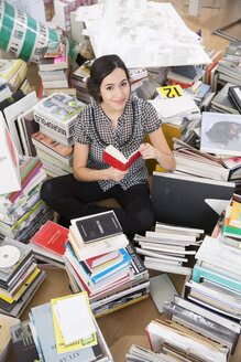 Smiling young woman sitting in the middle of piles of books - FK000414