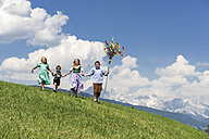 Austria, Salzburg State, Altenmarkt-Zauchensee, four children with Palmbusch running on alpine meadow - HHF004775