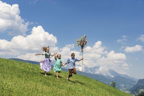 Austria, Salzburg State, Altenmarkt-Zauchensee, three children with Palmbusch running on alpine meadow - HHF004776