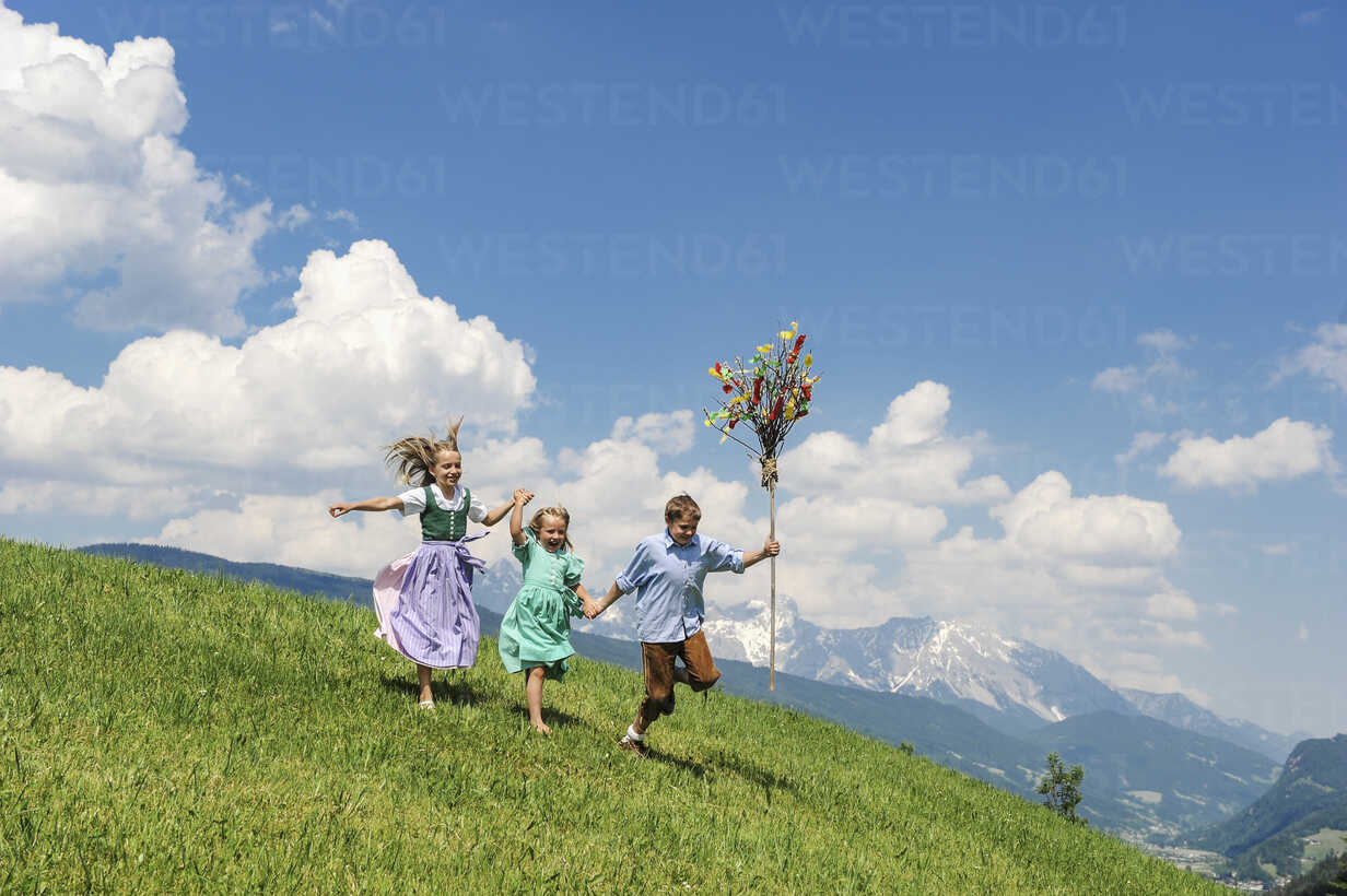 Austria, Salzburg State, Altenmarkt-Zauchensee, three children with Palmbusch running on alpine meadow - HHF004776 - Hans Huber/Westend61