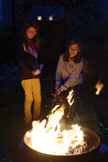 Germany, Upper Bavaria, two happy girls at the campfire at dusk - LB000612