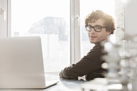Portrait of young architect sitting at desktop in his office - FKF000425