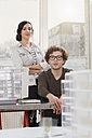 Portrait of two young architects with architectural model in office - FKF000460