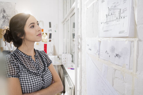 Portrait of young female architect looking at construction plan in office - FKF000435