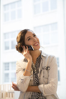 Portrait of young female architect telephoning in office - FKF000454