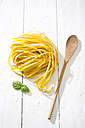 Tagliolini classico, leaves of basil, wooden spoon and flour on white wooden table - MAEF008079