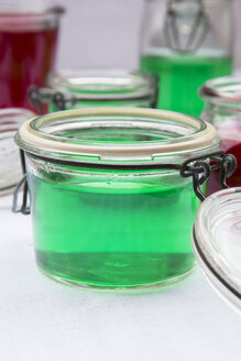 Preserving jars of woodruff and cherry jelly on white ground, close-up - LVF000795