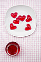 Plate of red hearts shaped of cherry jelly and preserving jar of cherry jelly on checkered cloth - LVF000794