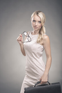 Portrait of a young businesswoman holding glasses and briefcase - VTF000137