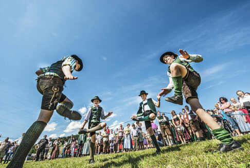 Austria, Irdning, Boys in traditional clothing dancing the Schuhplattler at May festival - HH004762