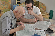 Grandson helping his grandfather by making tax declaration - LAF000649