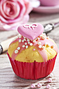Decorated muffin in muffin paper on laid table - CSF020948