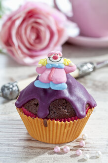 Decorated chocolate muffin in muffin paper on laid table - CSF020954