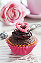 Decorated chocolate muffin in muffin paper on laid table - CSF020957