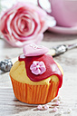 Decorated muffin in muffin paper on laid table - CSF020960