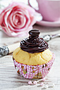 Decorated muffin in muffin paper on laid table - CSF020963