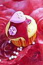 Decorated muffin in muffin paper on red floral design - CSF020969