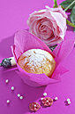 Muffin in pink wrap, rose blossom, cup and sugar beads on pink ground - CSF020978
