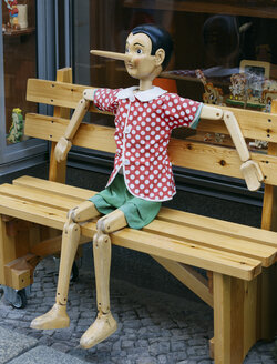 Full-size wooden pinocchio sitting on wooden bench in front of toy shop - HC000006