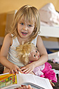 Portrait of little girl with doll and picture book - JFE000303