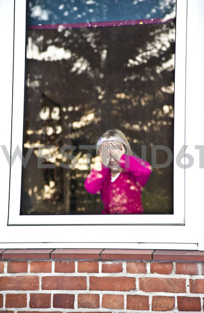 Little girl standing at window covering her eyes - JFEF000273