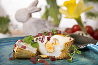 Egg muffin with ham cubes on plate and Easter bunny in background - CSTF000150