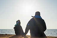 Germany, Mecklenburg-Western Pomerania, Ruegen, father and son looking at sea side by side - MJF000908