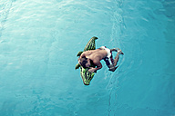 Young man with swim toy floating in water, view from above - PAF000551