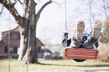 Germany, Mecklenburg-Western Pomerania, Ruegen, little boy swinging at playground - MJF000935