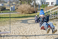 Germany, Mecklenburg-Western Pomerania, Ruegen, little boy swinging at playground - MJF000956