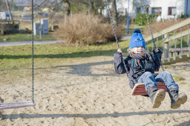 Germany, Mecklenburg-Western Pomerania, Ruegen, little boy swinging at playground - MJF000956