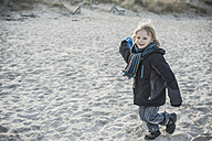 Germany, Mecklenburg-Western Pomerania, Ruegen, smiling little boy running on beach in winter - MJF000958