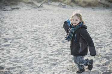 Germany, Mecklenburg-Western Pomerania, Ruegen, smiling little boy running on beach in winter - MJF000958