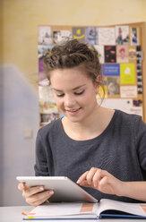 Female pupil using digital tablet while doing homework - BTF000321