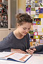 Female pupil with smartphone at her desk - BTF000322