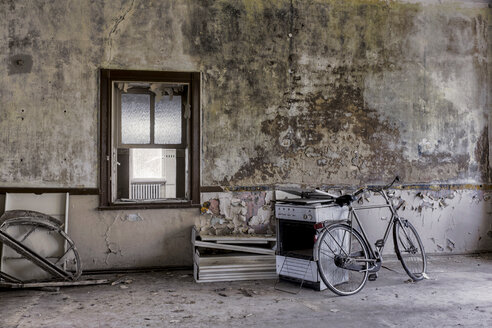 Germany, Thuringia, Erfurt, old bike and stove in abandoned room - HC000027
