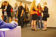 Young man sitting in party lounge with a drink in hand - HC000029