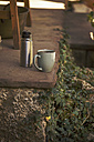 Cup of black coffee and thermos flask on stone step - EBSF000081