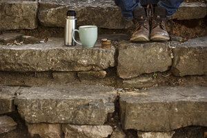 Feet of young man sitting on steps with cup of coffee and thermos flask having a break - EBSF000086
