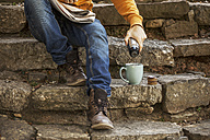 Young man sitting on steps having coffee break, partial view - EBSF000088