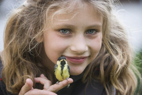 Portrait of smiling girl with great titmouse (Parus major) sitting on her finger - PA000557